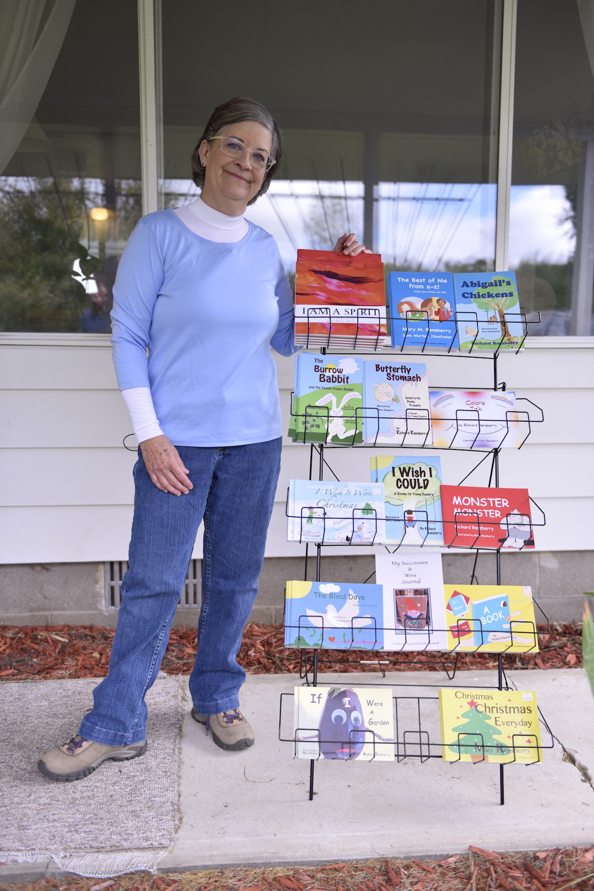 Michigan author and illustrator Mary Rensberry with an assortment of Books Make Booms custom books.